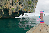 Longtail boat approaching limestone rock formation on Andaman Sea Thailand&#xA;<br />