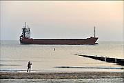 Nederland, Vlissingen, 14-9-2014 Een gastanker met LPG vaart bij Vlissingen vanaf de Westerschelde naar de Noordzee. Vanaf het strand van Walcheren bij Dishoek heb je mooi zicht op de scheepsbewegingen. Het is een kustvaarder. Een wandelaar maakt een foto.FOTO: FLIP FRANSSEN/ HOLLANDSE HOOGTE