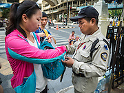03 SEPTEMBER 2015 - BANGKOK, THAILAND:   A security guard at Erawan Shrine checks tourists' bags at the gate to the shrine Thursday. Security at the shrine has been stepped up since the bombing. Repairs to Erawan Shrine were completed Thursday, Sept 3 after the shrine was bombed on August 17. Twenty people were killed in the bombing and more than 100 injured. The statue of the Four Faced Brahma in the shrine was damaged by shrapnel and a building at the shrine was damaged by debris.   PHOTO BY JACK KURTZ