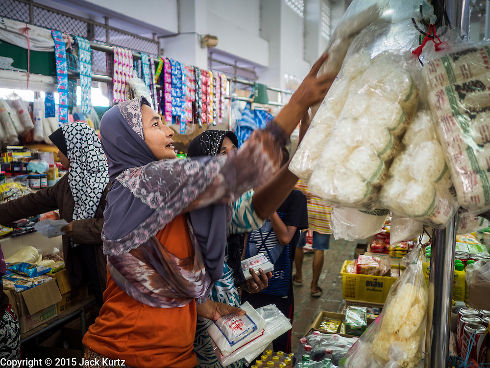 18 JUNE 2015 - PATTANI, PATTANI, THAILAND: A woman shops in the market in Pattani. Many Thai Muslims go shopping early in the day to buy food for Iftar, the meal that breaks the day long Ramadan fast.    PHOTO BY JACK KURTZ