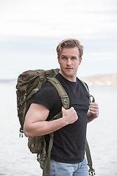 rugged blond hiker with a backpack outdoors by a river