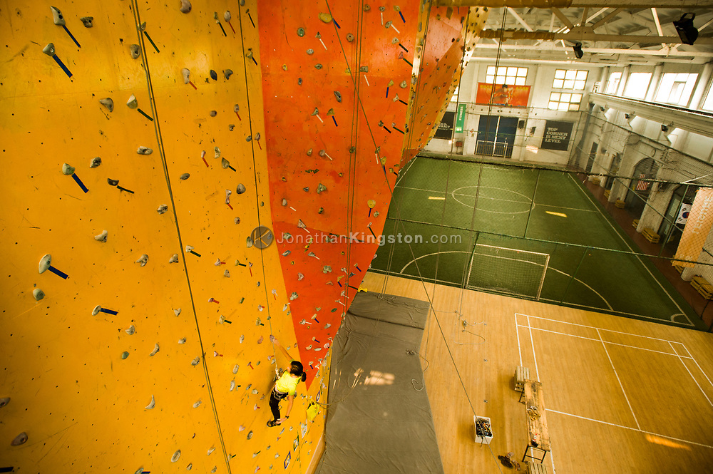 A woman scales a bright orange indoor rock climbing wall in Beijing, China (Model Released, Sean Ouyang, Rachel Ouyang).