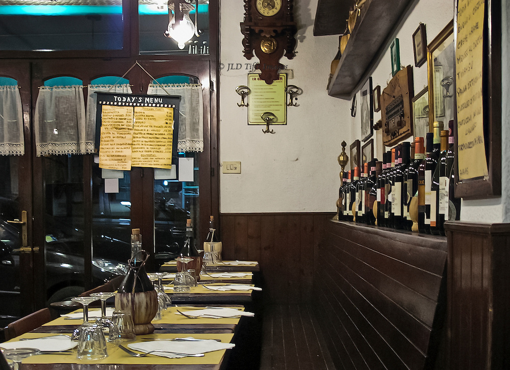 Interior, trattoria al Tranval.  Tables for two set along a bench; menu board posted over window; wine bottles in a rack above the bench.
