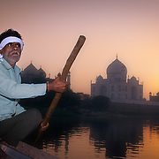 Agra, boatman in the Yamuna river and Taj Mahal at sunset