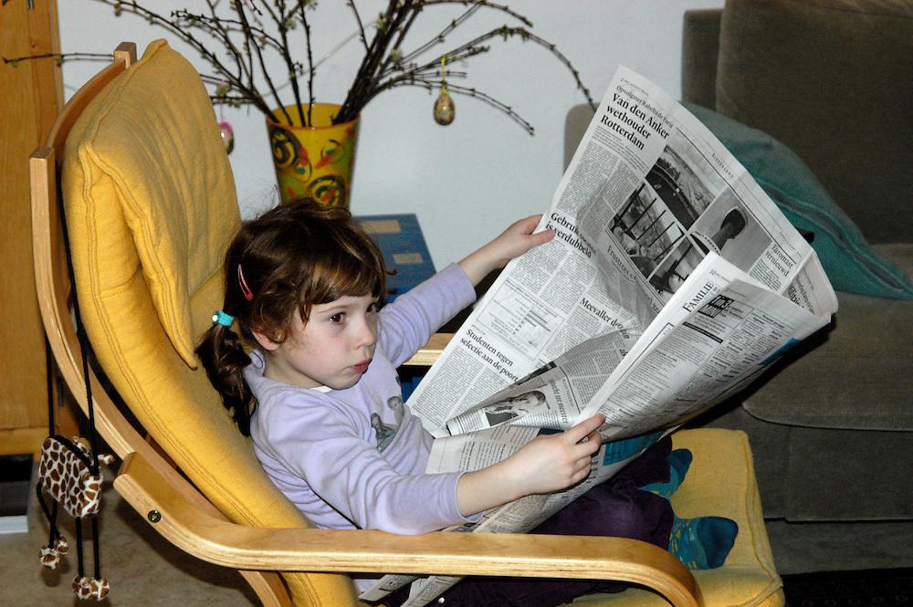 Nederland, Den Bosch, 20100510..Klein meisje leest de krant, NRC, en kijkt tegelijkertijd naar de televisie. .In de huiskamer in een IKEA stoel    .Gerlo Beernink/Hollandse Hoogte