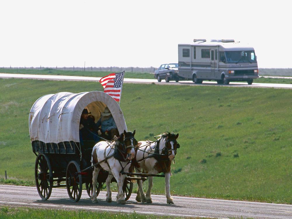 A recreational vehicle passes covered wagons and horseback riders on the modern South Dakota prairie outside Rapid City, South Dakota.