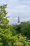 A church steeple rises above the trees on an overcast day, Quebec, Canada.