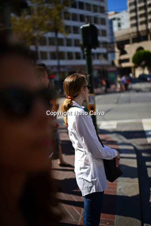 Woman waiting in crosswalk, San Francisco.