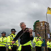 Anti-fracking  activists and protesters outside the gates of Quadrilla's fracking site June 31st, Lancashire, United Kingdom. A man plays violin outside the police cordon. The struggle against fracking in Lancashire has been going on for years. The fracking company Quadrilla is finally ready to bring in a drill tower to start drilling and anti-frackinhg activists are waiting in front of the gates to block the equipment getting in. Fracking is a destructive and potential dangerous and highly contentious method of extracting gas and this site will be the first of many in the United Kingdom reaching miles out under ground.