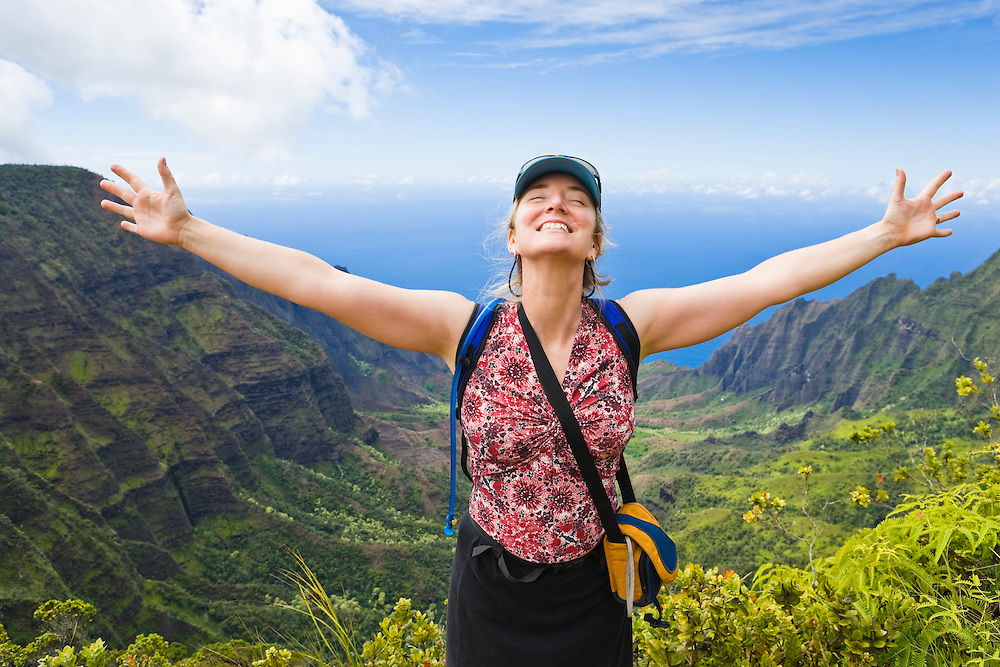 A late 30's early 40's woman on the Pihea Trail in Koke'e State Park overlooking the Kalalau Valley on the Na Pali Coast, Kauai, Hawaii
