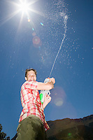 Portrait of teenage boy (16-17 years) spraying water from gun into air