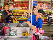 "05 OCTOBER 2012 - BANGKOK, THAILAND: A chestnut vendor sells chestnuts on Yaowarat Road in the Chinatown section of Bangkok, Thailand. Thailand in general, and Bangkok in particular, has a vibrant tradition of street food and ""eating on the run."" In recent years, Bangkok's street food has become something of an international landmark and is being written about in glossy travel magazines and in the pages of the New York Times.       PHOTO BY JACK KURTZ"