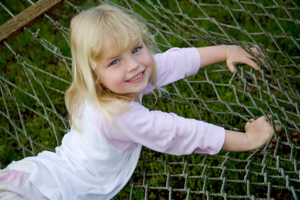 Girl (age 6) in pajamas on hammock, Powhatan, Virginia, United States  MR  PR