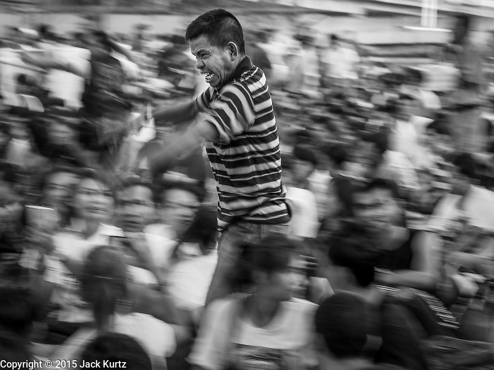 """07 MARCH 2015 - NAKHON CHAI SI, NAKHON PATHOM, THAILAND:  A man channeling the power of his sacred tattoo rushes the stage at the Wat Bang Phra tattoo festival. Wat Bang Phra is the best known """"Sak Yant"""" tattoo temple in Thailand. It's located in Nakhon Pathom province, about 40 miles from Bangkok. The tattoos are given with hollow stainless steel needles and are thought to possess magical powers of protection. The tattoos, which are given by Buddhist monks, are popular with soldiers, policeman and gangsters, people who generally live in harm's way. The tattoo must be activated to remain powerful and the annual Wai Khru Ceremony (tattoo festival) at the temple draws thousands of devotees who come to the temple to activate or renew the tattoos. People go into trance like states and then assume the personality of their tattoo, so people with tiger tattoos assume the personality of a tiger, people with monkey tattoos take on the personality of a monkey and so on. In recent years the tattoo festival has become popular with tourists who make the trip to Nakorn Pathom province to see a side of """"exotic"""" Thailand.   PHOTO BY JACK KURTZ"""