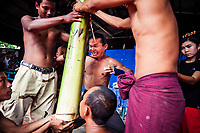 A Burmese man performs feats of strength for a crowd in Mandalay, Myanmar.