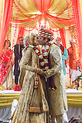 Baltimore, Maryland - December 20, 2014: After leaving the mandap, members of the audience yell for Trisha Satya Pasricha and Eshwan Ramudu to kiss. A traditional Indian marriage does not call for the couple to kiss. The couple, who met at Harvard, during a one of Trisha's student films, were married at the Baltimore Marriott Waterfront Hotel December 20, 2014. <br /> <br /> CREDIT: Matt Roth for The New York Times<br /> Assignment ID: 30168620A