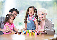 Happy three generation family playing with alphabet blocks at home