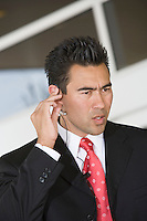 Business man using mobile phone with hands free, indoors