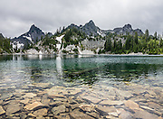 Kaleetan Peak (left, 6259 ft / 1908 m) rises above crystal-clear Gem Lake in Alpine Lakes Wilderness Area in the Cascade Range of Washington, USA. In mid July, we hiked to Gem Lake 10 miles round trip with 2800 feet cumulative gain along Snow Lake Trail #1013 in Mt. Baker-Snoqualmie National Forest. Take Interstate 90 Exit #52 westbound or Exit #53 eastbound and follow signs to Alpental Road ski area parking lot and trailhead. To avoid crowds at this popular trail, start early and avoid sunny weekends. The trail down from the saddle viewpoint to Snow Lake is often snow covered through July 4.