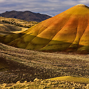 The sun creeps up on a late fall day over the Painted Hills Unit of John Day Fossil Beds National Monument, Oregon