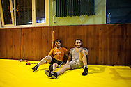 Ahmet Kiliç, right sits with a friend during a break in the training sessions held for both professional and hobbyist wrestlers in Istanbul.