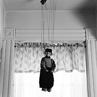 A puppet on strings hanging from the ceiling
