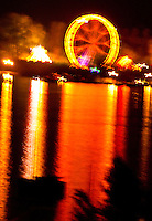Ticino, Southern Switzerland. Fiery reflection of a ferris wheel on Lago Maggiore.