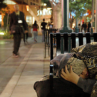 A homeless man sleeps on a bench at the Third Street Promenade on Wednesday, Sept. 13, 2007.
