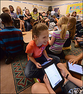 Marietta: Liv O'Kelley, 10, smiles as she works with classmates using iPads at Cheatham Hill Elementary School on Tuesday, August 21, 2013.  When it comes to technology, two classrooms of fifth graders are in charge of the lessons at Cheatham Hill Elementary School in West Cobb. Teachers and administrators at the school have figured out an important point: kids know more about technology than they do. So the lessons in these classes are student guided. ©2013 Johny Crawford