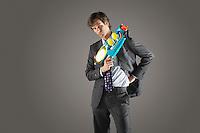Businessman standing holding water gun hand on hip