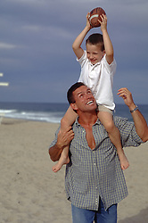 Father and son on the beach playing with a football