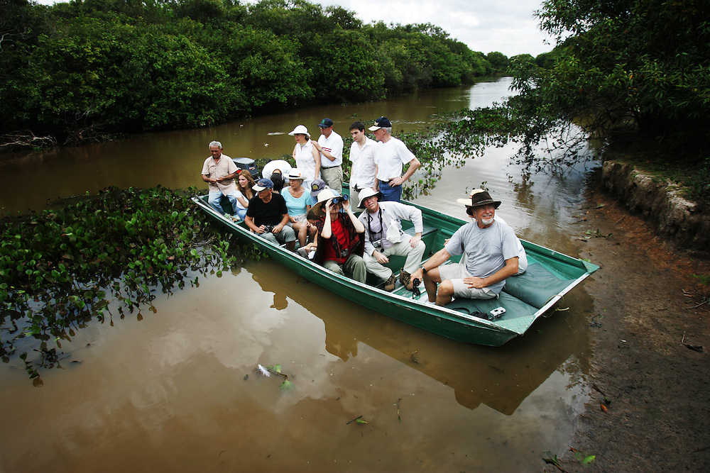 """A group of French tourists take a river boat cruise in Los Llanos in Venezuela. Los LLanos are the grasslands in western Venezuela famous for the """"llanera"""" culture of cowboys and music.  Many working """"Hatos"""" , or cattle ranches, dot the landscape of grasslands and river systems, offering tourists a chance to see the beautiful landscape and various wildlife.  Tourists go out on land and water excursions where they get a chance to see see caiman, orinoco crocodile, anaconda, piranha, numerous bird species and capybara, the world's largest rodent."""