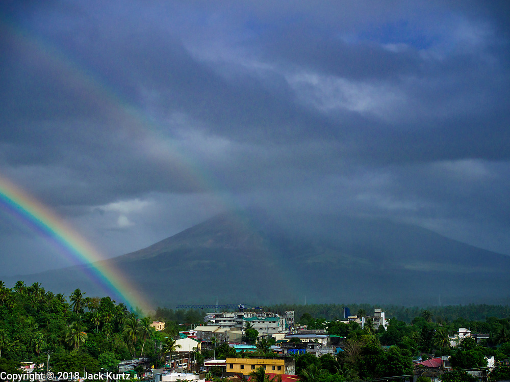 21 JANUARY 2018 - LEGAZPI, ALBAY, PHILIPPINES:  A double rainbow coming out of the Mayon volcano, as seen from Our Lady of the Gate Parish (Parroquia Nuestra Señora de la Porteria), releases smokes and ash Sunday morning. Mayon is the most active volcano in the Philippines. More than 30,000 people have been evacuated from communities on the near the Mayon volcano in Albay province in the Philippines. Most of the evacuees are staying at schools in communities outside of the evacuation zone.PHOTO BY JACK KURTZ