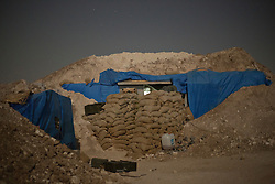© Licensed to London News Pictures. 01/09/2015. Bashiqa, Iraq. A sandbagged bunker, used an Iranian Kurdish peshmerga group called PAK, is seen on the summit of Bashiqa Mountain, Iraq, where the group man defensive position alongside their Iraqi-Kurdish counterparts.<br /> <br /> Bashiqa Mountain, towering over the town of the same name, is now a heavily fortified front line. Kurdish peshmerga, having withdrawn to the mountain after the August 2014 ISIS offensive, now watch over Islamic State held territory from their sandbagged high-ground positions. Regular exchanges of fire take place between the Kurds and the Islamic militants with the occupied Iraqi city of Mosul forming the backdrop.<br /> <br /> The town of Bashiqa, a formerly mixed town that had a population of Yazidi, Kurd, Arab and Shabak, now lies empty apart from insurgents. Along with several other urban sprawls the town forms one of the gateways to Iraq's second largest city that will need to be dealt with should the Kurds be called to advance on Mosul. Photo credit: Matt Cetti-Roberts/LNP