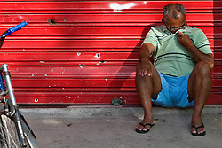 Um morador é visto próximo aos buracos de bala do tiroteio em uma porta na entrada da favela Morro do Alemão, em 27 de novembro de 2010 no Rio de Janeiro, Brasil.. Centenas de soldados e policiais se juntaram para uma repressão sobre as gangues de drogas. No início desta semana, a polícia forçou os membros das gangues saírem da favela Vila Cruzeiro, com o auxílio de tanques M113 transportadores blindados de pessoal. FOTO: Jefferson Bernardes/Preview.com
