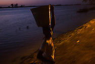 A boy carrying a bucket walks by the riverside ate dusk. At the confluence of the Niger and the Bani rivers, between Timbuktu and Ségou, Mopti is the second largest city in Mali, and the hub for commerce and tourism in this west-african landlocked country.