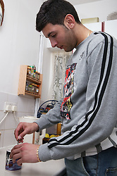 Young man in the kitchen making a mug of coffee; model released for use in HIV and Aids,
