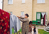 Mother hanging out washing with kids; Halifax; West Yorkshire