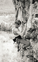 Young man rock climbing on a steep rock wall above a forest.