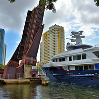 Rising Drawbridge for Yacht in Fort Lauderdale, Florida<br /> There are about a dozen drawbridges along the intercostal waterways of Broward County to accommodate the passing of enormous yachts.  Most of them elevate at scheduled times.  This one is a rail bridge operated by the Florida East Coast Railway.  It runs parallel to Moffat Avenue and crosses over the New River in the Riverwalk district.