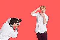 Male actor being photographed by paparazzi over red background