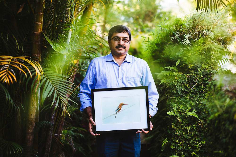 A portrait of Yashodan Heblekar with a painting of a white-breaster kingfisher at his home in Goa, India.
