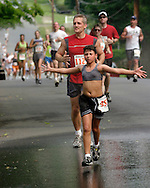 A girl opens her arms before getting cooled off in the spray from a spectator's hose during the 25th annual Orange Classic 10K road race in Middletown, N.Y., on June 11, 2005. The weather for the race was hot and humid.