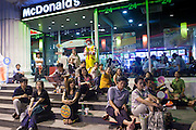 04 MAY 2010 - BANGKOK, THAILAND: Red Shirt protesters sit on the front steps of a McDonald's and listen to their speakers the main rally site in Ratchaprasong intersection in Bangkok Tuesday night. The Red Shirts have conditionally accepted the offer of Thai Prime Minister Abhisit Vejjajiva to dissolve parliament, investigate alleged human rights violations following the violence of April 10 and call for new elections in November of this year, 18 months earlier than they are currently scheduled, but they want more negotiation before they finalize any agreements. They said their protests would continue until a final agreement is reached. The Red Shirts, started their protest on March 13. They continue to call for Thai Prime Minister Abhisit Vejjajiva to step down and dissolve parliament immediately and demand the return of ousted Prime Minister Thaksin Shinawatra.     PHOTO BY JACK KURTZ