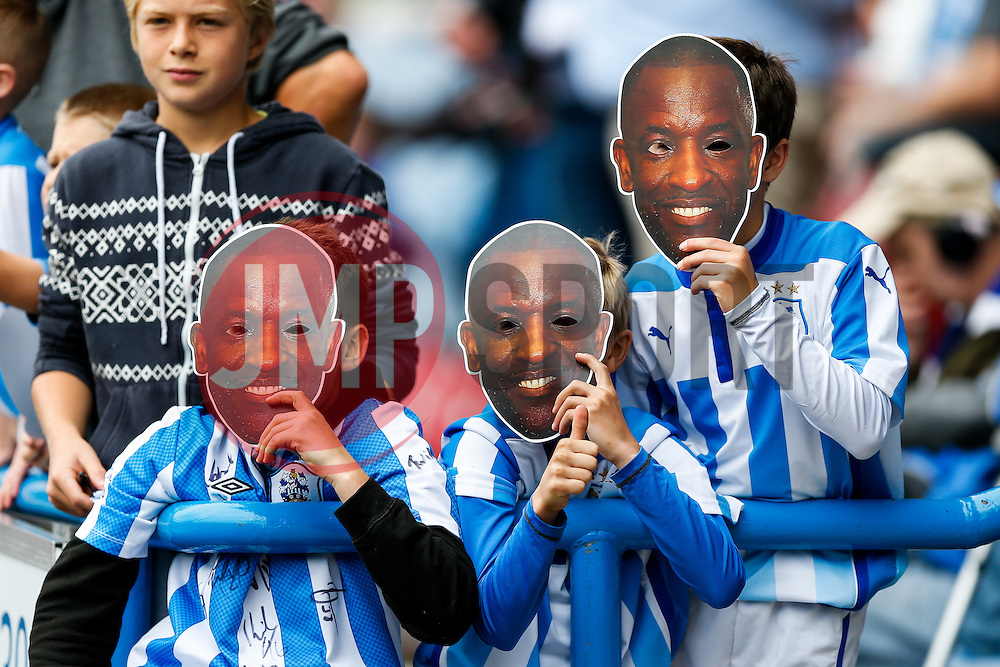 Young Huddersfield supporters hold face masks of their clubs new manager Chris Powell before his first game in charge - Photo mandatory by-line: Rogan Thomson/JMP - 07966 386802 - 13/09/2014 - SPORT - FOOTBALL - Huddersfield, England - The John Smith's Stadium - Huddersfield town v Middlesbrough - Sky Bet Championship.