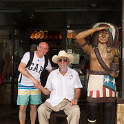 JUNE 9, 2016---MIAMI, FLORIDA<br /> A tourist poses for a photo with Pedro Bello, 88, as he sits smoking a cigar. He claims to smoke up to 20 cigars per day starting early in the morning. Bello and his son run the Cuba Tobacco Cigar Co., in the heart of Miami's Little Havana neighborhood.<br /> (Photo by Angel Valentin/Freelance)