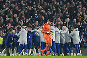 Chelsea players and staff celebrate as Tottenham Hotspur goalkeeper Paulo Gazzaniga (22) looks forlorn, walking off the pitch, during the EFL Cup semi final second leg match between Chelsea and Tottenham Hotspur at Stamford Bridge, London, England on 24 January 2019.