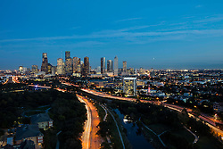 Aerial view of Houston skyline in the evening, featuring Buffalo Bayou Park and vehicle lights during rush hour traffic.