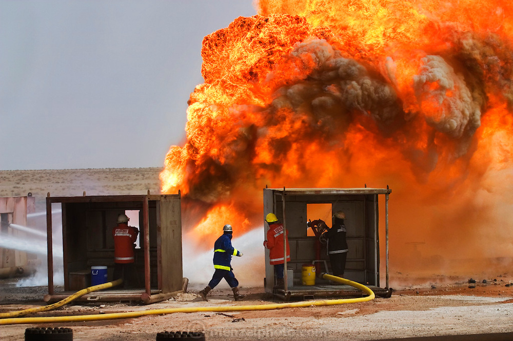 "Firefighters from the KWWK (Kuwait Wild Well Killers) attempt to kill an oil well fire in the Rumaila field by dousing it with high pressure water hoses. Then they will guide a ""stinger"" that will pump drilling mud into the damaged well. A ""stinger"" is a tapered pipe on the end of a long steel boom controlled by a bulldozer. Drilling mud, under high pressure, is pumped through the stinger into the well, stopping the flow of oil and gas. A wind shift after a sandstorm covered many of the men and machines in oil, a dangerous shift. The Rumaila field is one of Iraq's biggest oil fields with five billion barrels in reserve. Rumaila, Iraq. Rumaila is also spelled Rumeilah."