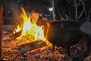 Cooking on an open campfire, an iron caldron on an outdoor wood fire